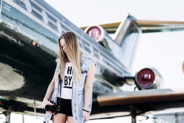 Belle fille touristique avec une vieille caméra vintage de film posant près de l'avion