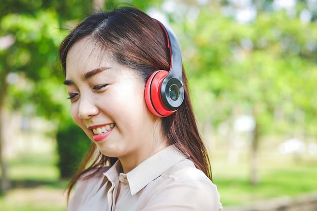 Belle fille travaillant au bureau avec des écouteurs sourire joyeusement
