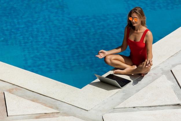 Belle fille travaille sur l'ordinateur près de la piscine
