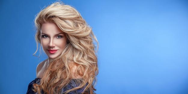 Belle fille avec un très gros cheveux longs ondulés luxueux en denim onbluebackground.