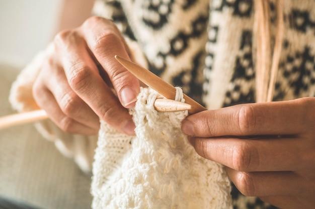 Belle fille tricote un pull chaud sur le lit. tricoter comme passe-temps. accessoires pour tricot.