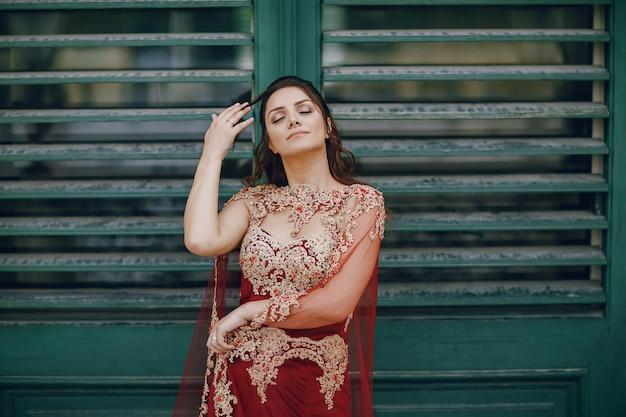 Une belle fille turque dans une longue robe rouge se promène dans la vieille ville d'été