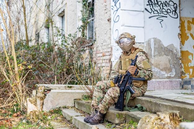Belle fille en uniforme militaire avec un pistolet airsoft assis sur les escaliers en face d'un bâtiment abandonné