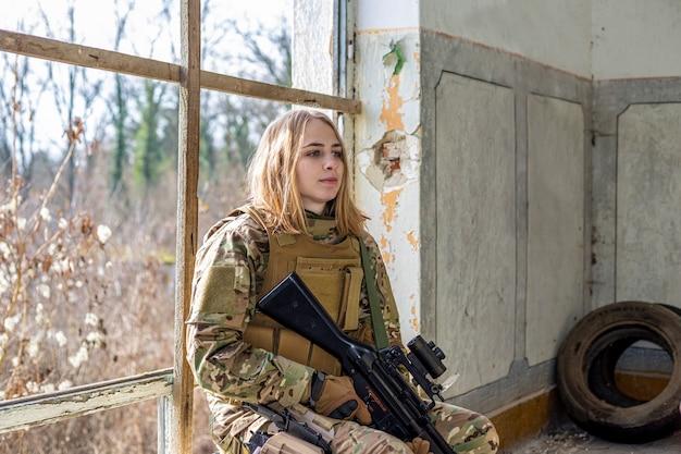 Belle fille en uniforme militaire avec un pistolet airsoft assis sur une fenêtre d'un bâtiment abandonné