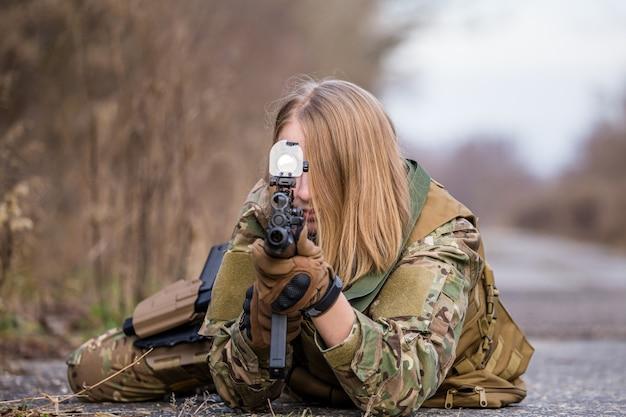 Belle fille en uniforme militaire avec un pistolet airsoft couché sur la route