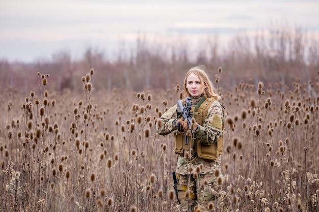 Une belle fille en uniforme militaire avec un pistolet airsoft debout dans le pré