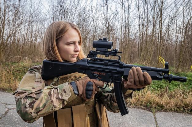 Belle fille en uniforme militaire avec un pistolet airsoft debout sur la route