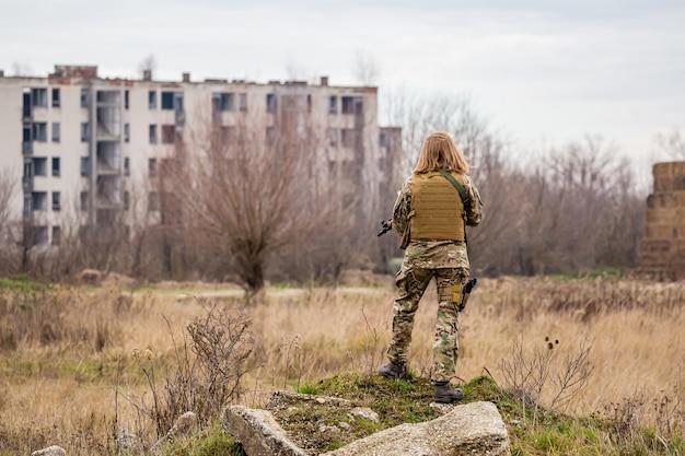 Une belle fille en uniforme militaire avec un pistolet airsoft debout sur un tas de pierre moussue avec des bâtiments en ruine en arrière-plan