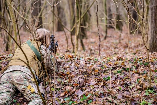 Belle fille en uniforme militaire avec un pistolet airsoft gisant sur le sol dans la forêt
