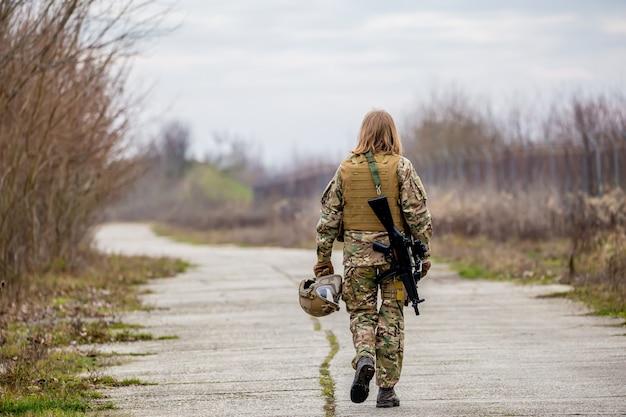 Belle fille en uniforme militaire avec un pistolet airsoft marchant sur la route