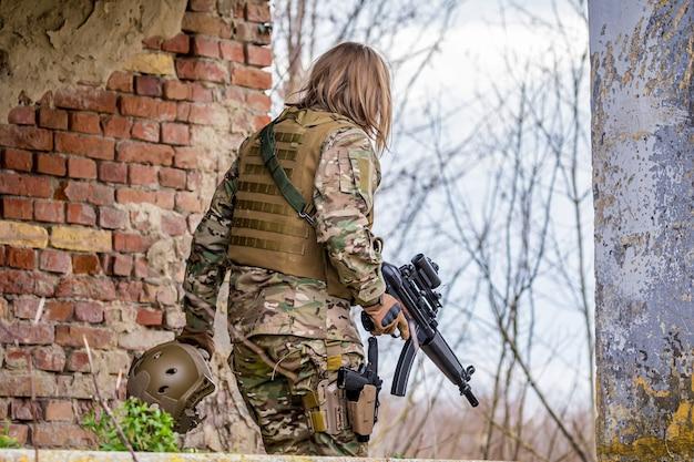 Belle fille en uniforme militaire avec un pistolet airsoft