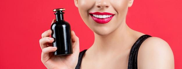 Belle fille utilisant du parfum. femme avec bouteille de parfum.