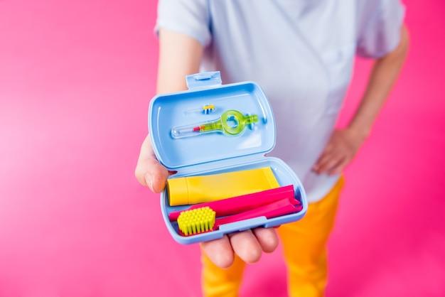 Belle fille utilise un kit de voyage pour les soins dentaires sur fond rose