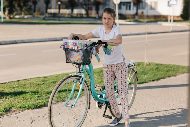 Belle fille sur un vélo bleu. fille fait du vélo. vacances d'été. passer du temps avec avantage. vélo femme avec panier