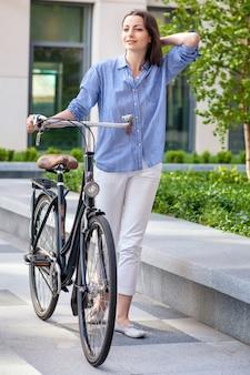 Belle fille avec un vélo sur route