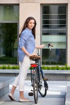 Belle fille avec un vélo sur la route