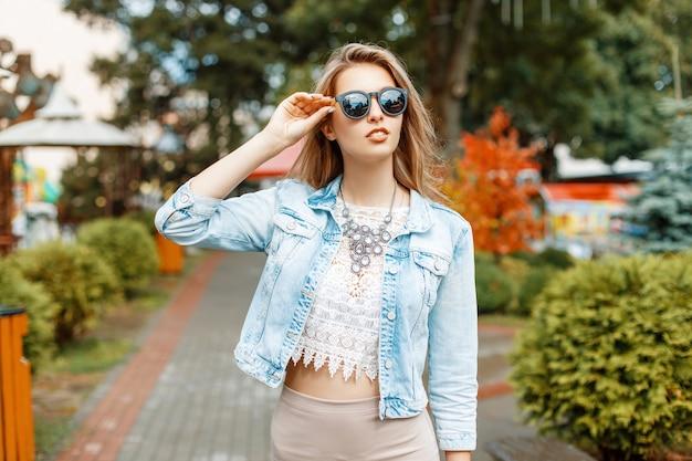 Belle fille en veste de lunettes de soleil et jeans marchant dans les attractions du parc