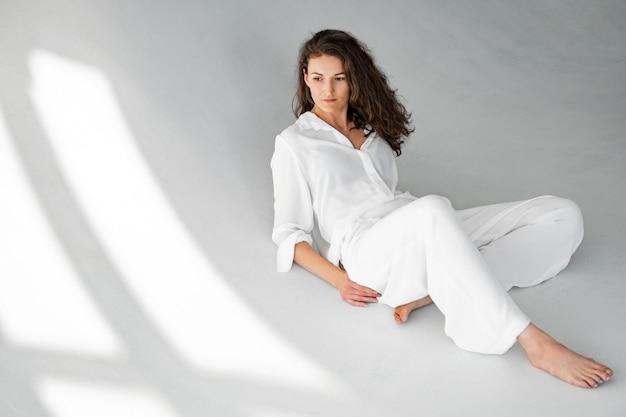Belle fille en vêtements blancs est assise sur le sol sur un mur blanc.