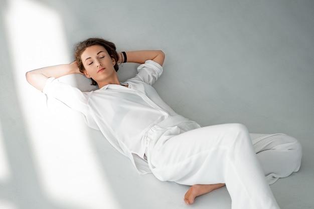 Belle fille en vêtements blancs est assise sur le sol.