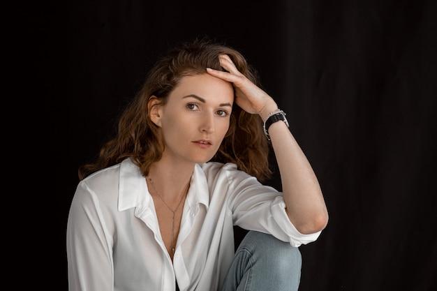 Belle fille en vêtements blancs. portrait d'une jolie femme d'âge moyen dans une pièce sombre.