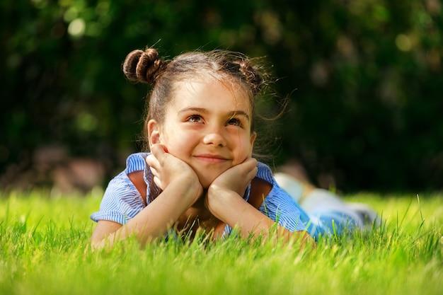 Une belle fille en vêtements bleus dans la nature en été dans le parc. enfant à la mode. photo de haute qualité