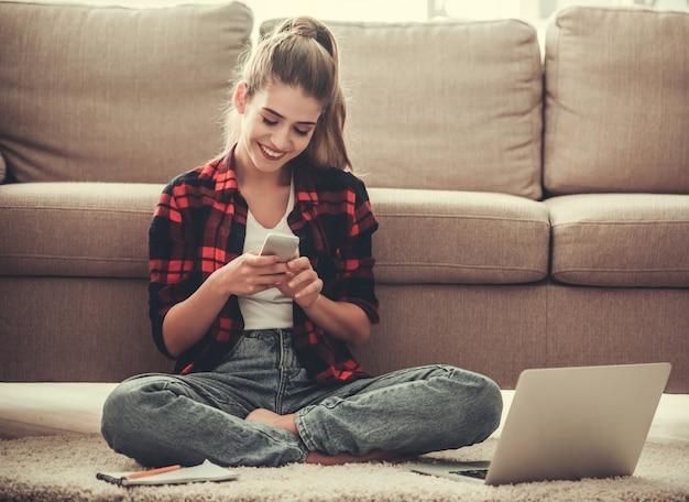 Belle fille en vêtements décontractés utilise un téléphone intelligent.