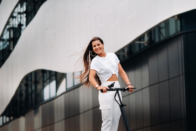 Belle fille en vêtements élégants blancs sur un scooter électrique dans la ville