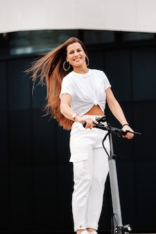 Belle fille en vêtements élégants blancs sur un scooter électrique dans la ville.