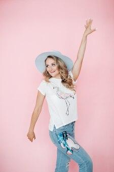 Belle fille en vêtements d'été se réjouit, photo isolée sur mur rose
