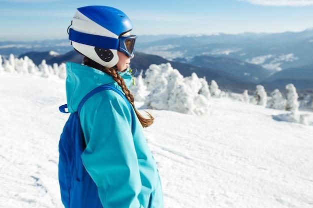 Une belle fille en vêtements d'hiver, un casque bleu et une veste verte passe un bon moment dans les montagnes.