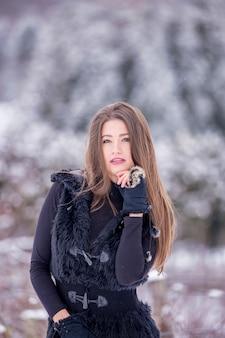 Une belle fille en vêtements noirs en hiver