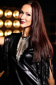 Belle fille en vêtements noirs posant avec des lumières de studio