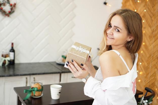 Belle fille vêtue d'une chemise blanche tenant un cadeau dans une cuisine moderne et lumineuse