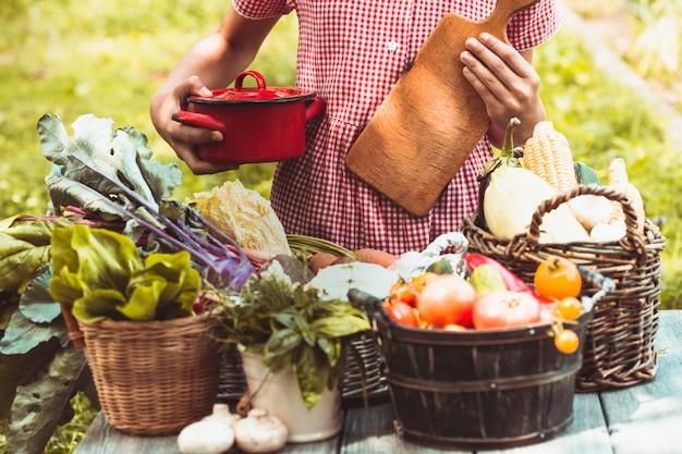 Belle fille vêtue d'une robe à carreaux joue avec une variété de légumes sur la pelouse