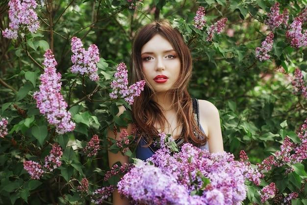 Belle fille vêtue d'une robe posant dans un buisson de lilas