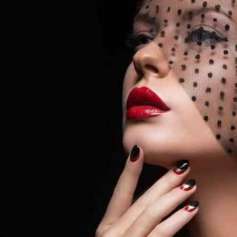 Belle fille avec un voile, un maquillage de soirée, des ongles noirs et rouges.