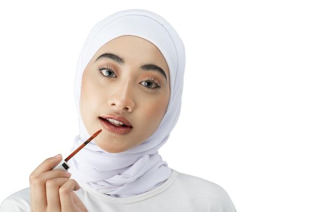 Belle fille voilée asiatique vêtue d'une robe moderne regardant la caméra à l'aide de rouge à lèvres