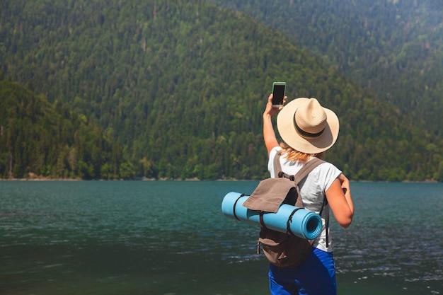 Belle fille voyageur fait selfie sur un grand lac de montagne bleue dans le fond des montagnes