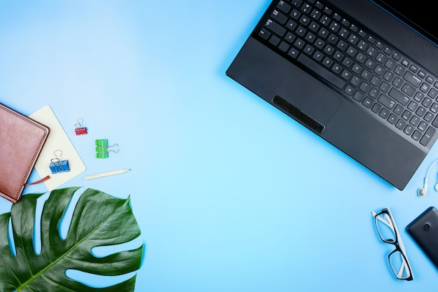 Belle flatlay avec un ordinateur portable, des lunettes, des feuilles de philodendron et d'autres accessoires professionnels. concept d'un bureau à domicile. mise à plat.