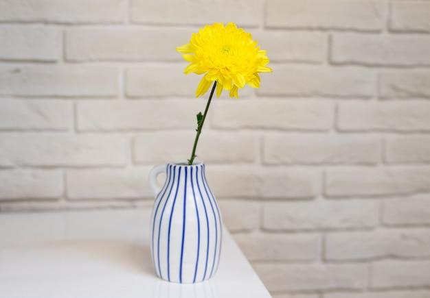 Belle fleur jaune dans un vase blanc avec des rayures bleues surface de texture blanche