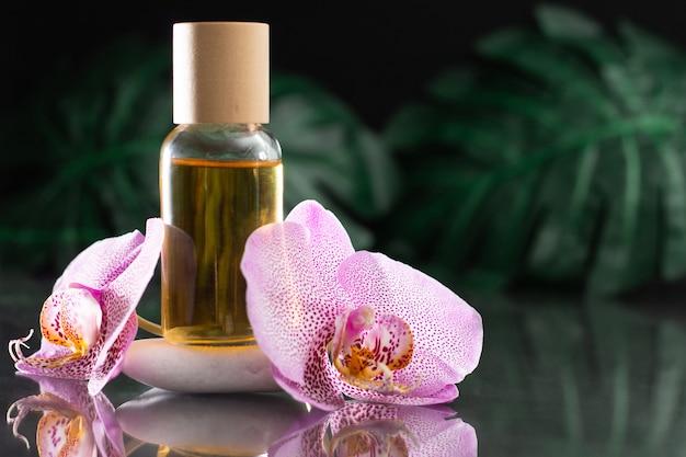 Belle fleur d'orchidée lilas et bouteille en verre transparent d'huile jaune ou de parfum debout sur la pierre blanche avec des feuilles de monstera sur une surface réfléchissante noire