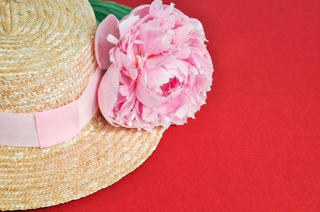Belle fleur de pivoine rose à côté du chapeau de paille sur le rouge.
