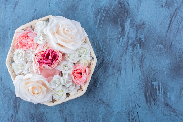 Belle fleur rose colorée dans un panier en osier sur bleu.