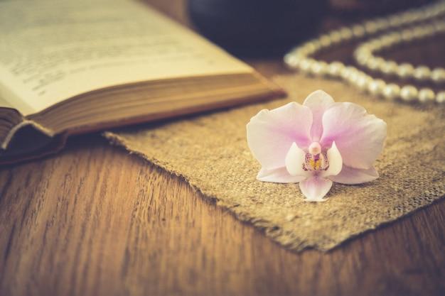 Belle fleur avec vieux livre et tasse de café ou de thé. fond romantique avec effet de filtre rétro