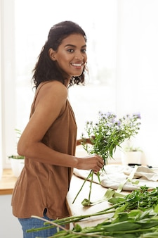 Belle fleuriste femme africaine souriant tenant des fleurs. mur blanc.
