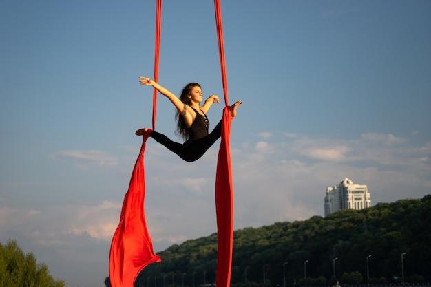 Belle et flexible artiste de cirque féminin dansant avec de la soie aérienne avec le ciel et le littoral de la rivière sur fond.