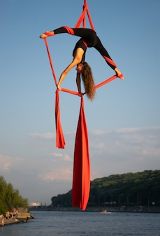 Belle et flexible artiste de cirque féminin dansant avec de la soie aérienne avec le ciel et le littoral de la rivière