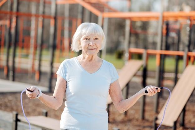 Belle forme. femme mince exubérante à la corde à sauter lors de l'exercice en plein air