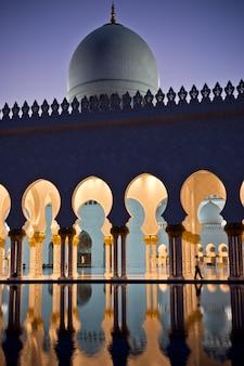 Belle galerie de la célèbre mosquée blanche sheikh zayed à abu dhabi, émirats arabes unis la nuit