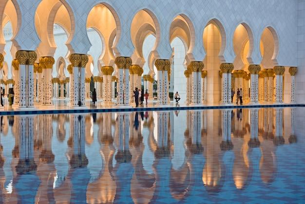 Belle galerie de la célèbre mosquée blanche sheikh zayed à abu dhabi, émirats arabes unis. reflets au coucher du soleil